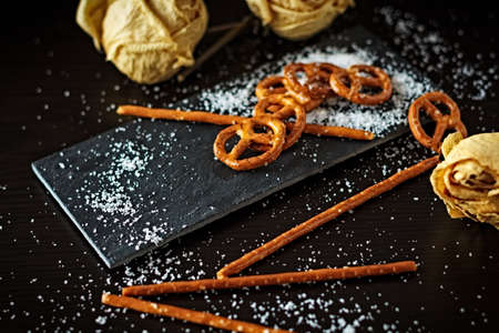 Typical German Bretzel. German food and snack. Delicious savory appetizer for lunch. Salted cracker bottom on slate bottom Stock Photo