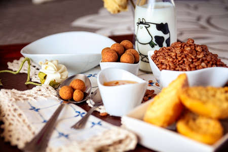 Tray with continental breakfast on hotel bed made of cereals, Cinnamon Balls, chocolate, cakes and a bowl with spoon. Breakfast in bed. Front view. Stock Photo