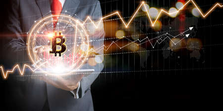 Businessman with Bitcoin currency and gold market exchange graphs. Stock market concept Zdjęcie Seryjne