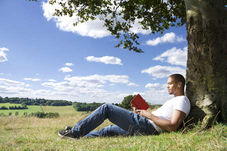 individuals: Man Reading a Book under a Tree