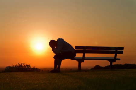 depression: Man in Distress against the setting sun background Stock Photo