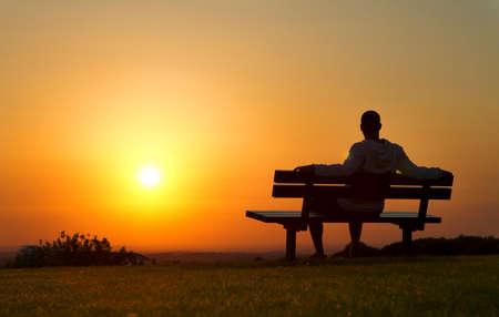banc de parc: Un homme assis sur un banc en appr�ciant la vue d'un coucher de soleil Banque d'images