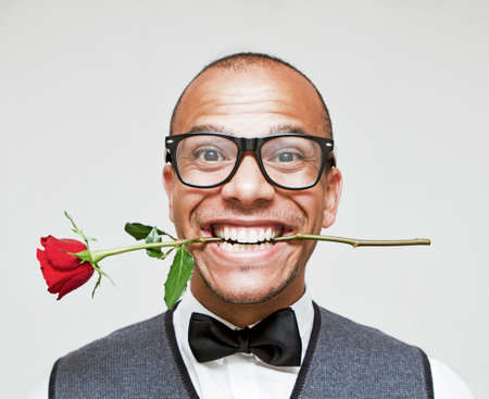 Male Geek holding a rose suggestively between his teeth photo