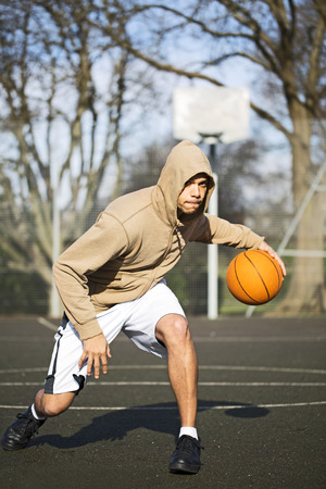 bouncing: Portrait of hooded male basketball player