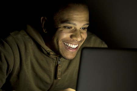 Young smiling man on laptop at night photo