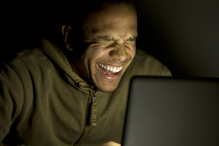 Young laughing man on laptop at night photo