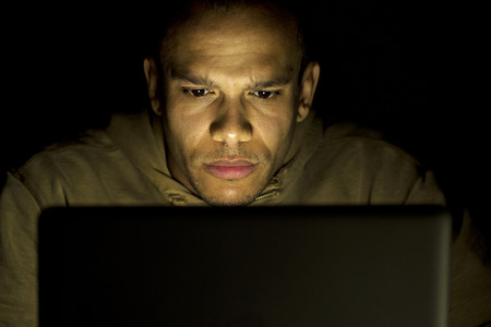 Young man concentrating on his laptop at night photo