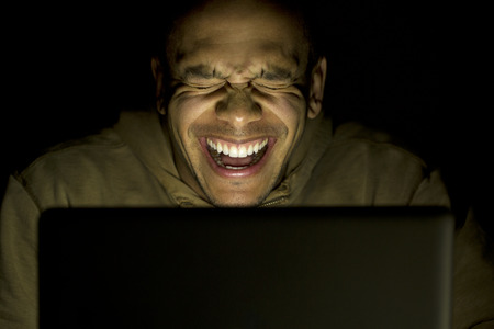 hilarity: Young laughing man on his laptop at night Stock Photo