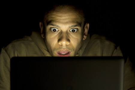 dark room: Young shocked man on his laptop at night