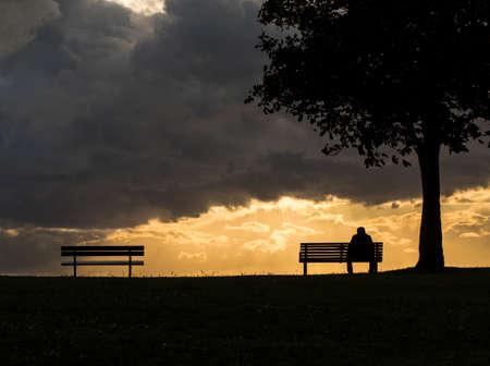 hombre solo: Figura la silueta sentada en un banco al atardecer