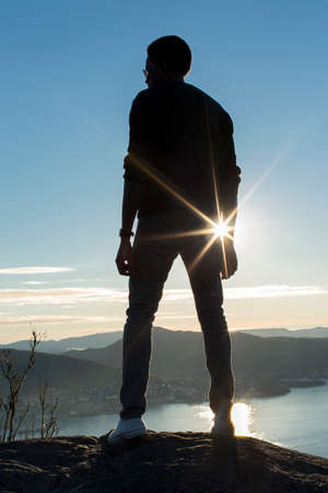 gazing: Silhouette man on a mountain top with sun flare
