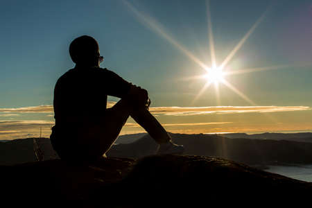 views of the mountains: Silhouette man sitting on a mountain top watching the sunset Stock Photo