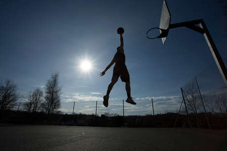 dunk: Basketball player slam dunk silhouette Stock Photo