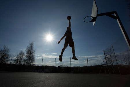 Basketball player slam dunk silhouette Stock Photo