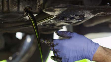 mecanico automotriz: Mec�nico de drenaje de aceite de un coche Foto de archivo