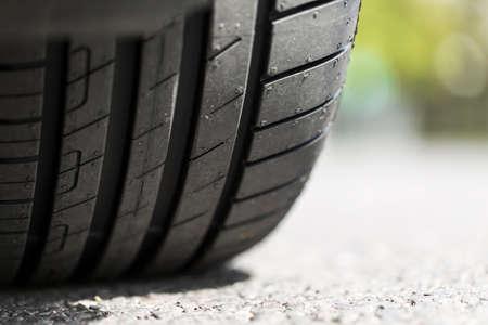 pisar: Close up de la banda de rodadura del neumático de coche en la carretera