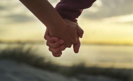 parejas caminando: Pareja de la mano en una playa al atardecer Foto de archivo
