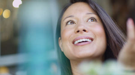 asian lifestyle: Attractive young woman with a cheerful face as she talks to an unseen friend Stock Photo