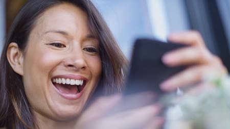 sees: Attractive woman laughing as she sees something on her phone