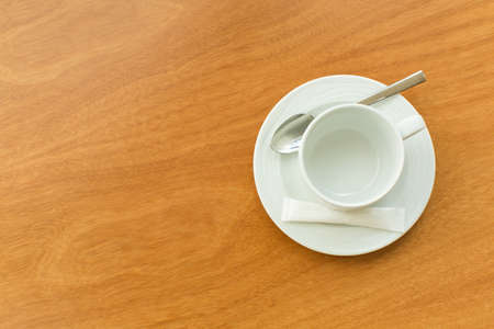 sugar spoon: Empty white cup and saucer with a silver spoon and as ache of sugar on a wooden table Stock Photo