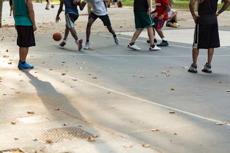 engaging: Unrecognized basketball players engaging in a game on an outdoor court in a park with leaves scattered about, shallow focus. Stock Photo