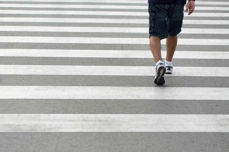 crossing legs: Legs of a man wearing shorts and sneakers walking across a zebra crossing Stock Photo