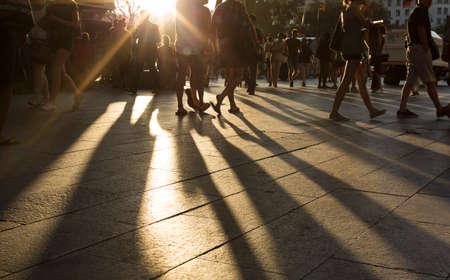 caminando: Multitudes caminando en un distrito de la ciudad ocupada como las llamaradas del sol entre ellos en la tarde creando largas sombras sobre el terreno