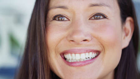 young woman face: Close up portrait of an attractive young woman smiling slightly off camera