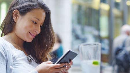 personen: Aantrekkelijke jonge vrouw zat op een terrasje zacht glimlacht als ze kijkt naar haar telefoon