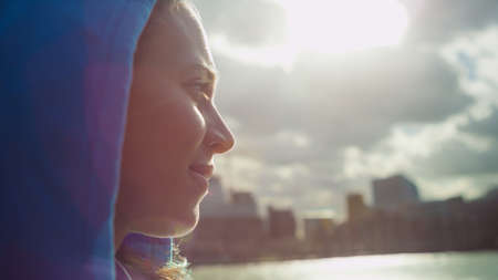 looking out: Side portrait of an attractive woman in a hood looking out to the city over a river on a sunny day, with sun flare Stock Photo