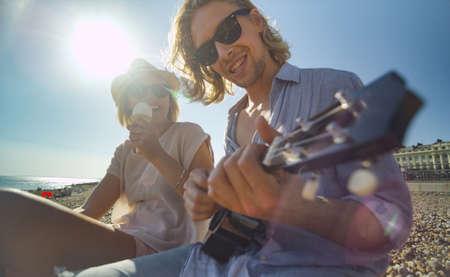 comiendo helado: Enfriar pareja en una playa que se divierte con un instrumento musical y helado