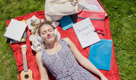 finishing school: Young girl relaxing in the sun after finishing her school work