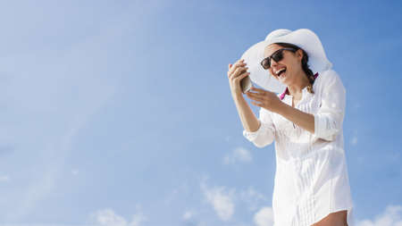 caftan: Young fashionable woman using her phone on a beautiful day