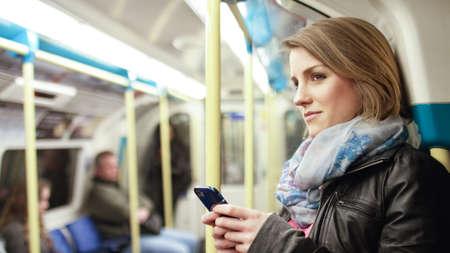 personas pensando: Mujer atractiva en un tren subterráneo sonríe a algo fuera de cámara