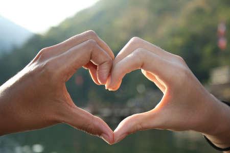 romantics: Silhouette of hands in heart shape  Stock Photo