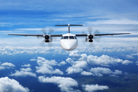 A passenger plane flying high in the sky above the clouds, close up, front view