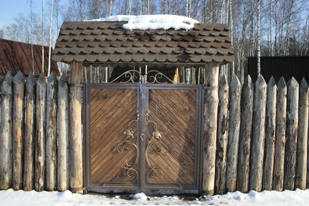 gad: Gate and fence from dry pine peaked logs Stock Photo