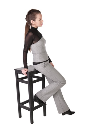 The girl has leant the elbows on a bar chair, isolated on a white background photo
