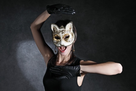 The young girl in the Venetian mask of a cat against a dark background photo