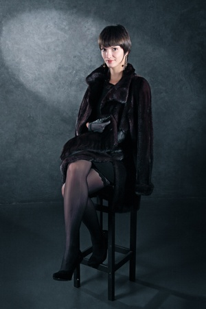 The girl in a fur coat sits on a bar chair against a dark wall photo