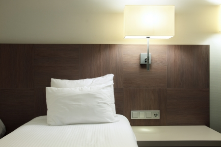 Bed, little table and lamp in a small room of hotel photo