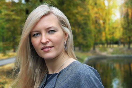 Portrait long-haired blonde against autumn park