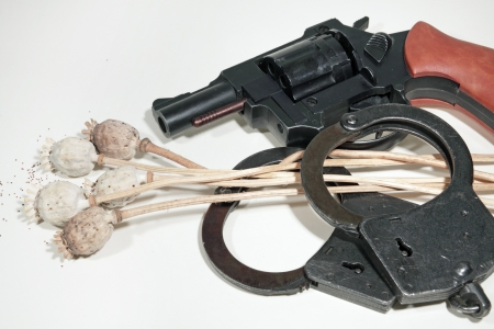 transgression: Dry poppy, revolver and handcuffs on a white background Stock Photo