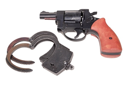culprit: Black handcuffs and revolver isolated on white background Stock Photo