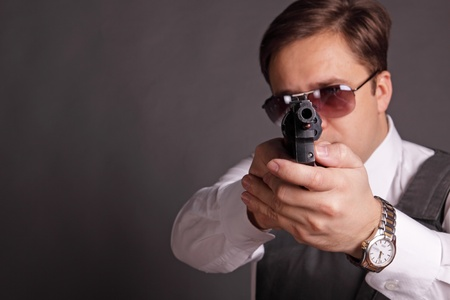 The man in a bullet-proof vest and sun glasses aims from a revolver Stock Photo