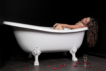The sexy girl lies in a white bath on a black background photo
