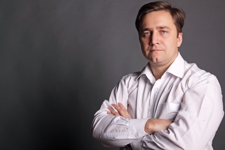 deplorable: Portrait of the man in a white shirt on a dark grey background Stock Photo