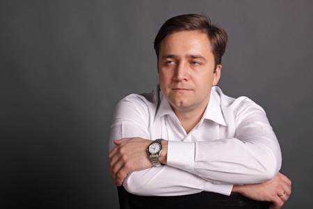 Portrait of the man in a white shirt on a dark grey background Stock Photo