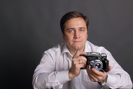 portly: The man in a white shirt with the ancient camera on darkly grey background