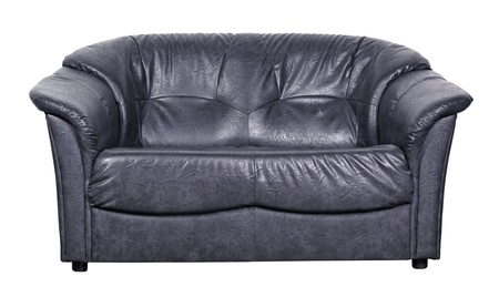 leathern: Black leather sofa about a white wall on brown tiled to a floor Stock Photo